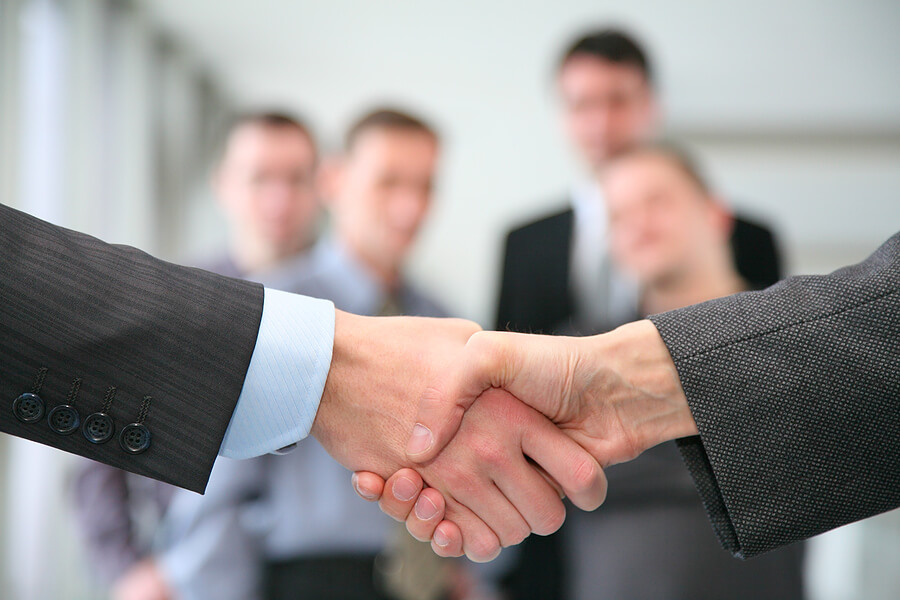 Corporate-Handshake-with-business-people-in-the-background